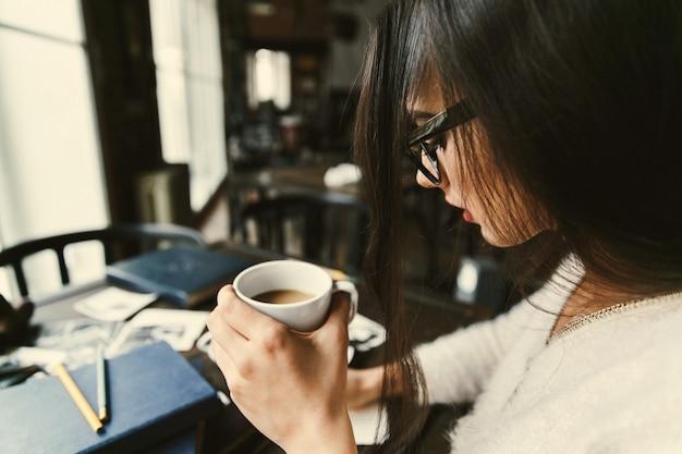 長い髪の女の子は、カフェのテーブルでコーヒーを飲む