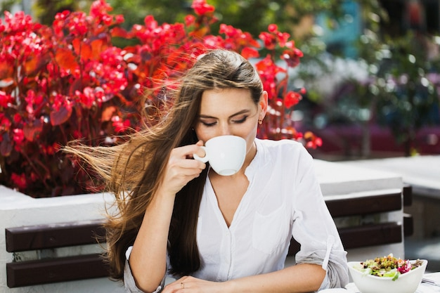 Девушка с длинными волосами выпивает кофе, сидя в ресторане
