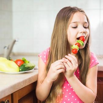 Girl with long hair eating salad skewer