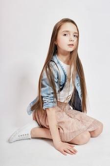 風になびく長い髪の少女と薄ピンクの背景にポーズをとるデニムジャケット。若いモデル、トレーニング、写真のポーズ