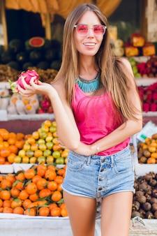 Ragazza con capelli lunghi e buon corpo sul mercato dei frutti tropicali. indossa occhiali da sole rosa, tiene il frutto della passione e sorride
