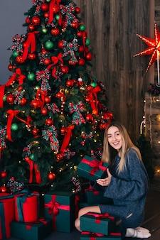 灰色のセーターを着た長い髪の少女がクリスマスツリーの近くに座って贈り物を持っています。花輪と星を背景にした暖炉。