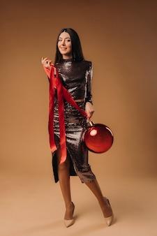 茶色の背景に大きなクリスマスボールと光沢のあるドレスを着た長い髪の少女。