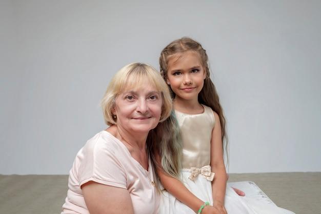 彼女のシニアおばあちゃんの白い背景の家族のスタジオ撮影でお祝いのドレスを着た長い髪の少女