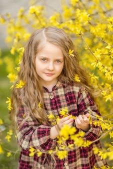 黄色い花の長い髪の少女。レンギョウを背景にした子供。子供の春の肖像画