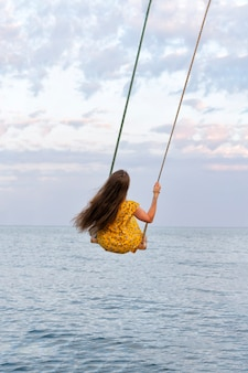 Girl with long hair is riding swing above the water. vertical frame.