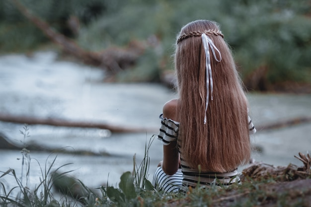 Girl with a long hair, looking on the breathtaking view on the lake .