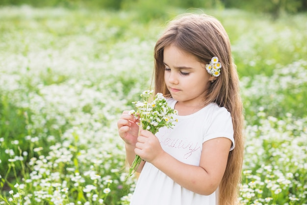 Girl with long hair looking at white flowers collected by her in field
