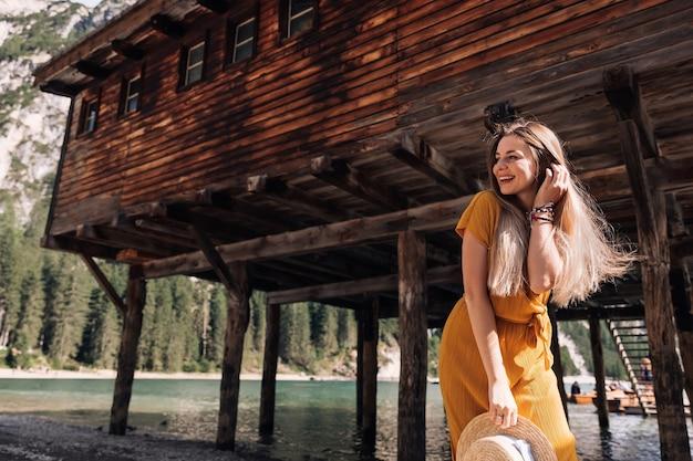 山の湖のそばの木造の建物の近くでポーズをとる長い髪の少女。ドレスとカンカン帽の若い女性。