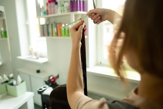 Девушка с длинными волосами сидит в салоне красоты и подстригает волосы крупным планом