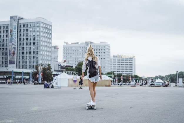 Girl with long hair skates on a skateboard. street, active sports