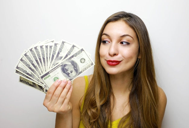 Girl with long hair standing over white background holding money banknotes