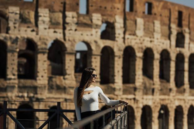 Girl with long hair in stylish clothes posing near colosseum in rome