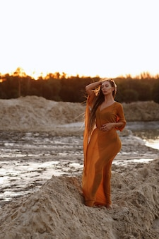 Girl with long hair in a transparent cape in the sands in the summer at sunset