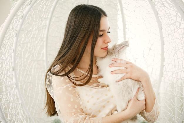 긴 머리를 가진 소녀. 여자의 팔에 흰 토끼.