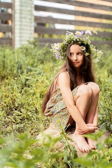 Girl with long hair with a wreath of flowers on her head is sitting on a stone