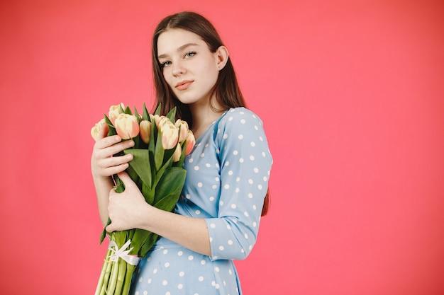 긴 머리를 가진 소녀. 꽃의 꽃다발을 가진 여자입니다. 파란 드레스에 아가씨.