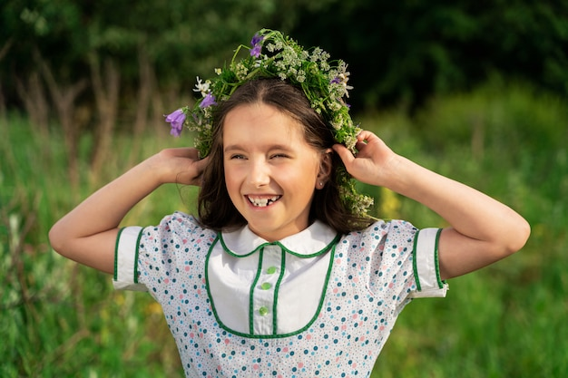 Girl with long hair and a wreath of flowers laughs