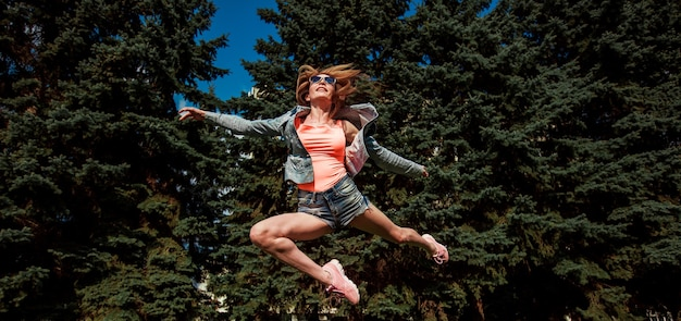 A girl with long legs in shorts and an orange blouse jumps like a ballerina. banner panorama