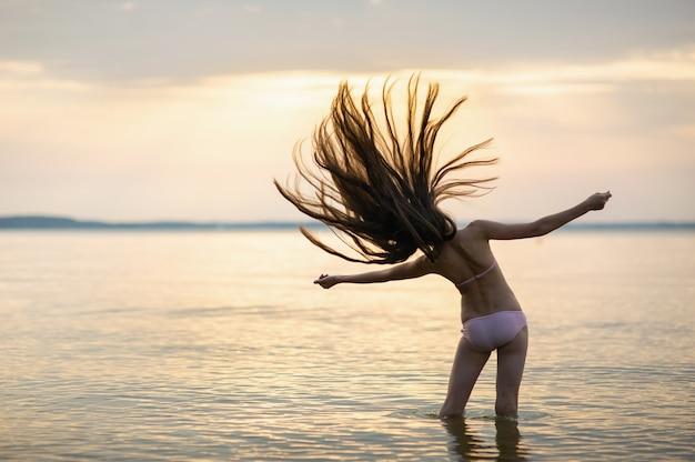일몰 동안 바다에 느슨한 머리를 가진 소녀