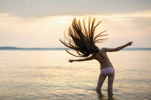 Girl with loose hair on the sea during sunset