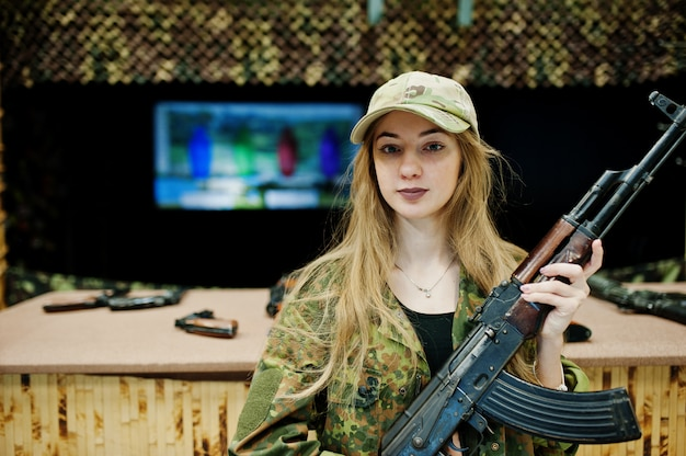 Girl with machine gun at hands on shooting range.