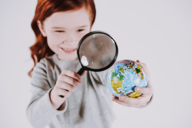 Girl with magnifying glass is studying globe.