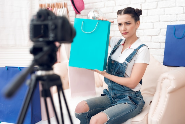 Girl with make up holds up colorful bag to camera