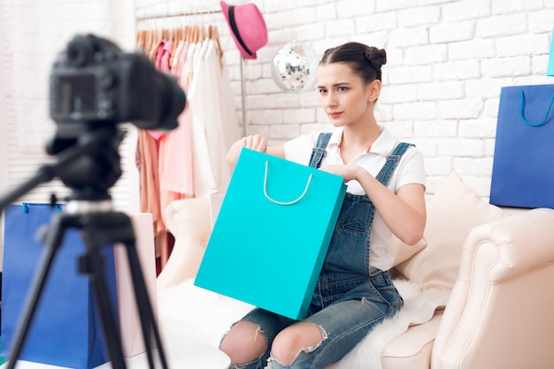 Girl with make up presents colorful bag to camera.