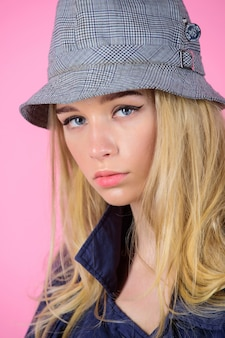 Девушка с макияжем носит широкополую шляпу. концепция моды девушка. мода и стиль. блондинка фотомодель на розовом фоне. загадочное лицо женщины носить шляпу. уверенно и модно. современный стиль.