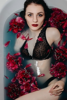 Girl with makeup in bra lies and enjoys in bath with peonies