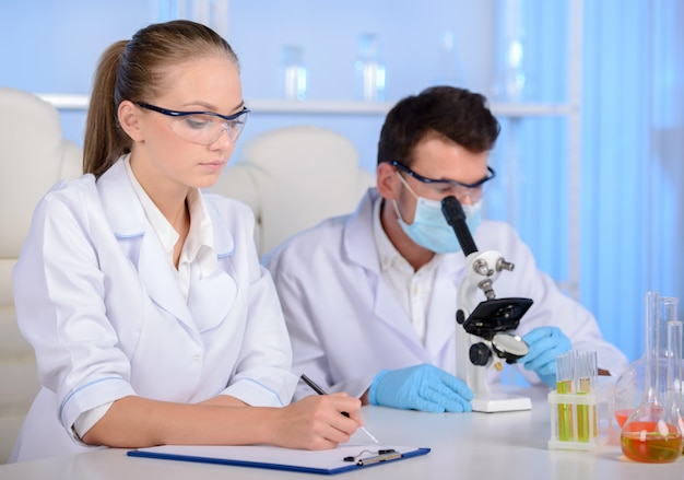 Girl with a man in laboratory and conduct an experiment.