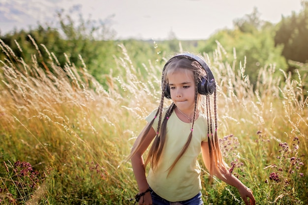 Girl with many braids and headphones listening music and dancing among flower field