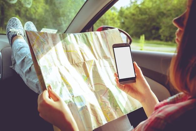 車の中で手で地図と電話を持つ少女