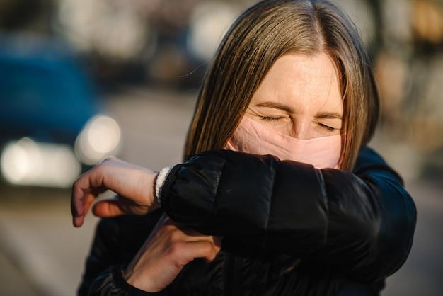 Девушка с маской во время панического кашля covid-19 на улице. опасности коронавируса. риск распространения инфекции. прикрывать нос и рот, чихать согнутым локтем. женский кашель в профилактике рук.