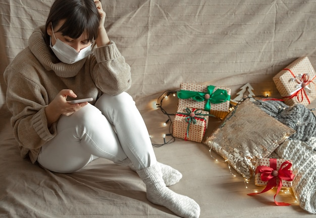 A girl with a mask on her face buys christmas gifts online in the phone. christmas shopping concept during the coronavirus pandemic.