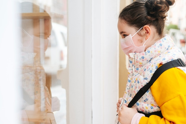 A girl with a mask on her face looks at a shop window. the girl is wearing a yellow sweater and backpack