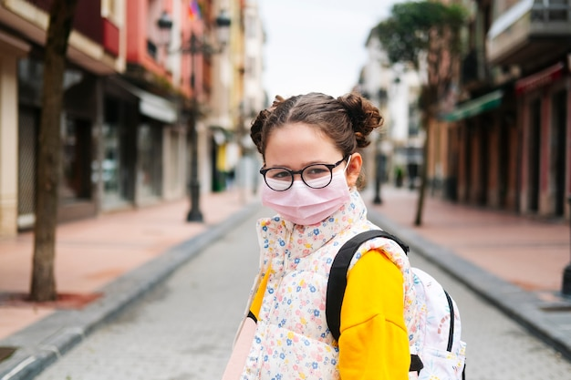 A girl with a mask on her face in the street of a city