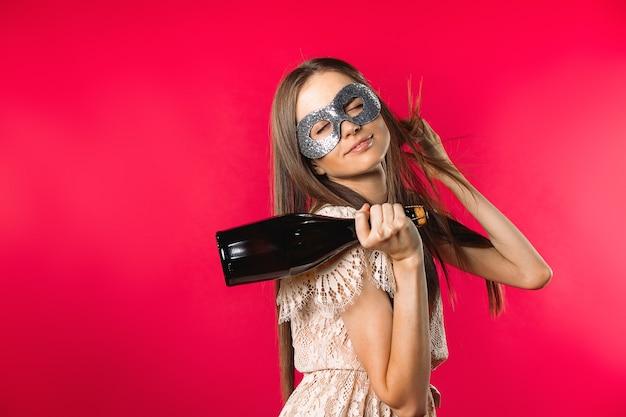 Девушка с маскарадной маской и шампанским в праздничном настроении на красном фоне