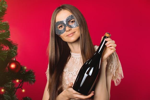 Девушка с маскарадной маской и шампанским рядом с деревом на красном фоне