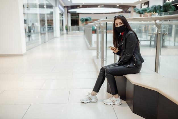 ショッピングセンターで医療用黒いマスクと携帯電話を持つ少女。コロナウイルスパンデミック。ショッピングセンターにマスクをした女性が立っています。保護マスクをした女の子がショッピングモールで買い物をしています。