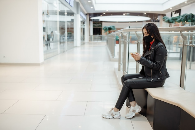 医療の黒いマスクとショッピングセンターでの携帯電話を持つ少女。コロナウイルスパンデミック。