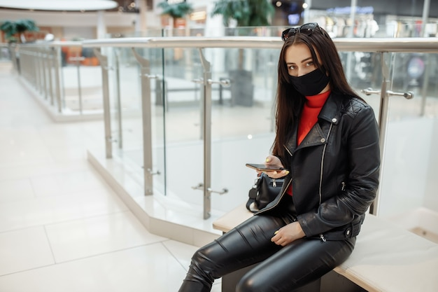 Девушка с медицинской черной маской и мобильным телефоном в торговом центре. .