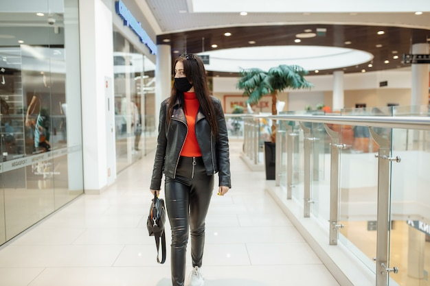 A girl with a medical black mask is walking along a shopping center.
