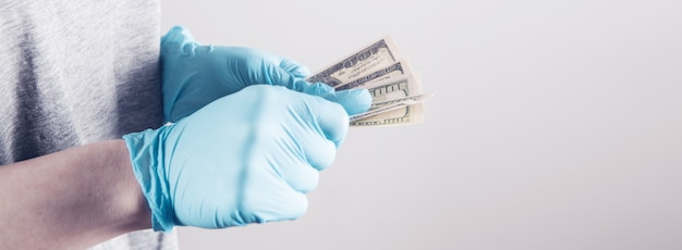 돈을 들고 의료 장갑을 가진 소녀