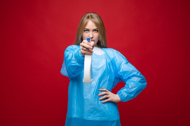 Girl with medical gown using antibacterial spray