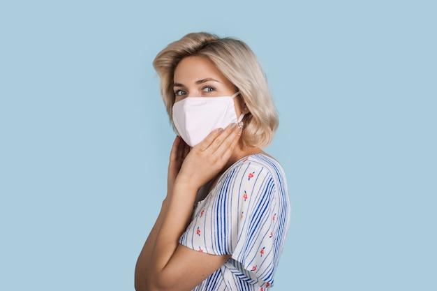 医療マスクを持つ少女はカメラに微笑んでいます
