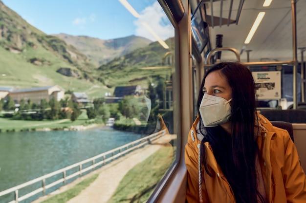 기차에서 창 밖을 바라보는 의료 마스크를 쓴 소녀
