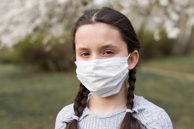 Girl with medical mask outdoors