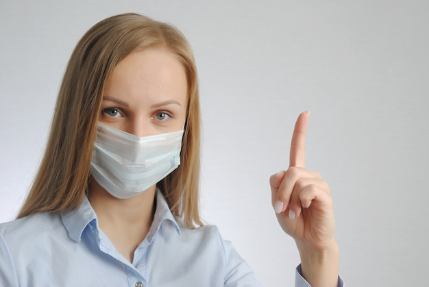 医療用マスクの女の子が指を上に向ける